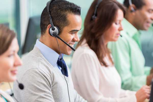 Cheerful mid adult Hispanic male IT support person smiles while talking with customer on the phone. He is wearing a headset. His colleagues are working in the foreground and the background.